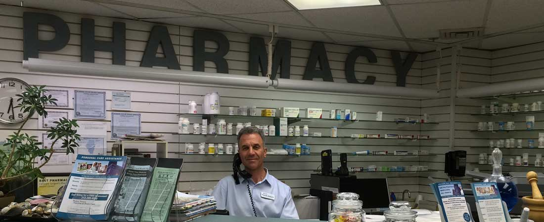 Pharmacist Mark Paley standing behind the pharmacy counter at Carnegie Sargent's Pharmacy